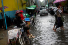 A driver sits on his bicycle rickshaw in a street flooded with rain water in Yangon, Myanmar. Photo / AP
