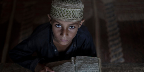 An Afghan refugee looks up while reading verses of the Quran during the holy fasting month of Ramadan in a mosque on the outskirts of Islamabad, Pakistan. Photo / AP