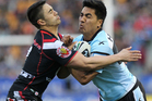 Shaun Johnson tackles Cronulla's Sosaia Feki during the round 21 NRL match between the New Zealand Warriors and the Cronulla Sharks. Photo / Getty Images.