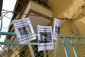 Banners against former German SS officer Erich Priebke reading'he costs us 1 million euros each year' outside his home where he is under house arrest. Photo / AFP
