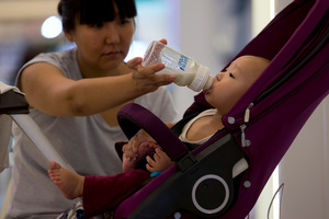 A woman feeds milk to her baby on a stroller at a shopping mall in Beijing. Photo / AP