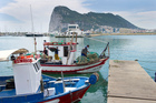 Spanish fishing boats sit moored in La Linea de Concepcion, Spain, in front of Gibraltar.  Photo / AP
