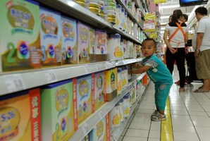 A toddler plays in the imported baby products section while his parents purchase baby products in a Beijing supermarket. Photo / AFP