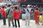 Onlookers watch a cremation. Photo / Sonam Sherpa