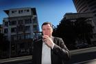 Jonathan Milne smokes a cigarette outside APN house. Photo / Doug Sherring