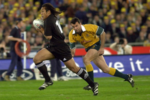 Tana Umaga leaves Joe Roff gasping as he opens the scoring just 90 seconds into the game. Photo / Getty Images