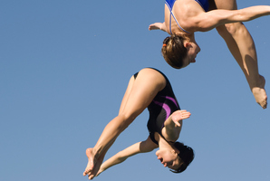Two women diving from diving board.