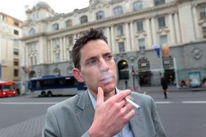 John Weekes gauges reactions to his e-cigarette at Britomart. Photo / Doug Sherring