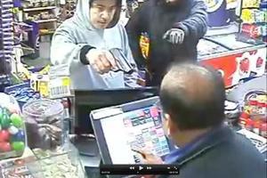 The robbers, one armed, threaten shopkeeper Ravi Khattar.