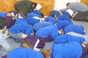 Children and staff drop, cover and hold as they've been taught at St Mary's School, Carterton, during today's 6.2 quake. Photo / Gerald Ford