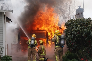 Firefighters battle to save a Masterton property yesterday as a residential garage is engulfed in flames. Photo / APN