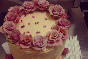 The raspberry, white chocolate and coconut birthday cake with rose water vanilla cream cheese icing, decorated with antique roses and dried wild rose petals, made by The Caker. Photo / Jordan Rondel