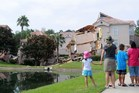 People look at a partially collapsed building over a sinkhole at Summer Bay Resort near Disney World. Photo / AFP