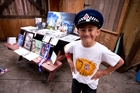 Mason, 8, with memorabilia of his policeman dad Kali Fungavaka, who died a year ago in Tonga. Photo / Dean Purcell