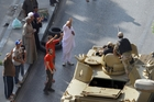 Egyptians greet soldiers riding in an armoured vehicle on their way to secure positions near Torah prison in Cairo. Photo / AP