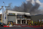 Firefighters using foam to fight a blaze at Racetech in Petone. Photo / Mark Mitchell