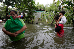 Residents wade through floodwaters after receiving relief goods from a non-government organization. Photo / AP