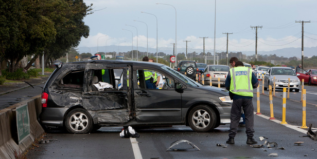Police begin their initial investigations at the entrance to Hawke's Bay Airport yesterday after a car and logging truck collided. Photo / Glenn Taylor