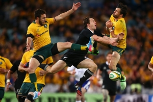 High-flying All Black wing Ben Smith contests the ball with Wallabies Nic White, left, and Adam Ashley Cooper in Sydney. Photo / Getty Images