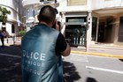 A forensic policeman takes a picture as he investigates outside the Kronometry shop on July 31, 2013, after two armed men held up a store selling luxury watches in the French Riviera town of Cannes, t