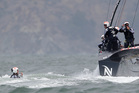 Team NZ skipper Dean Barker looks on as Rob Waddell surfaces. Photo / AP