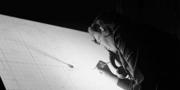 A Women's Auxiliary Air Force member plots a position on the map.