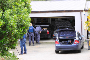 Police search a North Shore property after the arrest of a man over the death of a woman in a dog attack. Photo / Chris Loufte