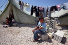 A Syrian refugee boy sits outside his tent next to his family at a temporary refugee camp.Photo / AP