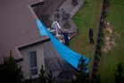 A tarpaulin hangs from the end of the house protecting an area of deck of interest to police investigators.