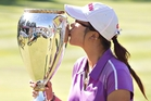 Lydia Ko kisses her second Canadian Open trophy at Edmonton yesterday but batted away questions about turning professional. Photo / AP