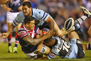 Sonny Bill Williams of the Roosters offloads during his side's defeat to the Sharks. Photo / Getty Images