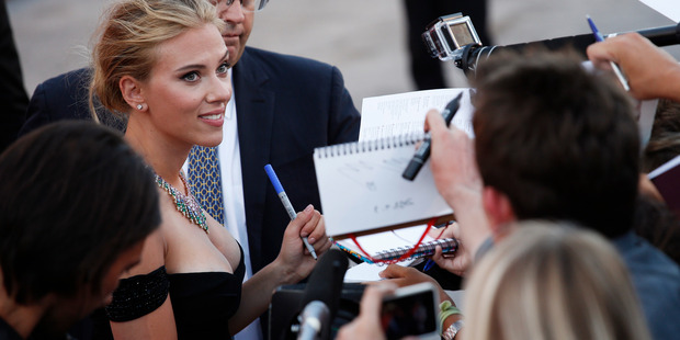 Actress Scarlett Johansson signs autographs for members of the public as she arrives on the red carpet at the Venice Film Festival. Photo / AP