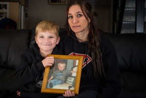 Valeria Tokoar and her son Ashton, 7, hold a picture of her late son Tyreese, killed on a driveway. Photo / Michael Craig