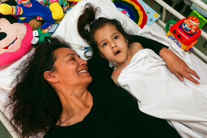 Kathleen McKay lies with her terminally ill daughter, Brennagh, in Wellington Hospital. Photo / Getty Images