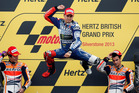 Jorge Lorenzo of Spain jumps on the podium after winning the MotoGP race of the British Grand Prix at the Silverstone circuit in Silverstone, England. Photo / AP