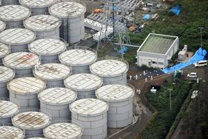 Workers stand on storage tanks at the Fukushima Dai-ichi nuclear plant at Okuma town in Fukushima prefecture, northeastern Japan. Photo / AFP