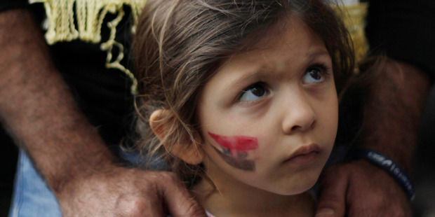 A girl with the Syrian flag painted on her cheek attends a demonstration by adults protesting any military action in Syria by the U.S., outside the U.S. embassy in Caracas, Venezuela. Photo / AP