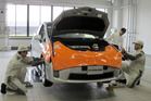Mechanics work on Prius at a newly completed Toyota's service center in Tajimi, central Japan, Monday, July 22, 2013.