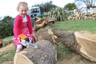 HARD WORK: Bella Glover, 4, on High St in Masterton, pretends to saw up fallen trees on her property. PHOTO/ANDREW BONALLACK