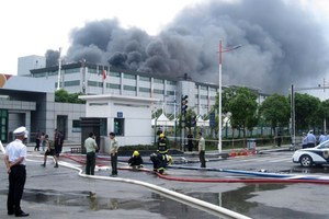 Emergency personnel at the scene as heavy smoke rises from the SK Hynix facility. Photo / AFP