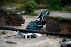 Three vehicles sit in water after crashing where a road collapsed following flooding at Highway 287 and Dillon at the Broomfield/Lafayette border, Colorado. Photo / AP