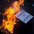 A sign burns during a march against US intervention in Syria in Buenos Aires, Argentina. Photo / AP