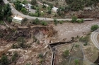 This aerial photo shows a  raging waterfall destroying a bridge along Highway 34 toward Estes Park, Colo.