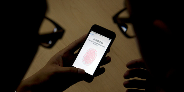 An Apple employee, right, instructs a journalist on the use of the fingerprint scanner technology built into the company's iPhone 5S during a media event held in Beijing, China. Photo / AP