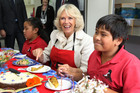 The Duchess of Cornwall enjoys a piece of carrot cake made in the school's kitchen as part of their Garden to Table curriculum. Photo / NZH