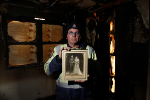 Fire investigator Craig Bain holds a photo taken from the wreckage of Pearl's home. Photo / File