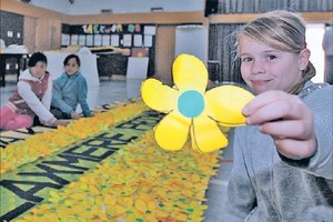 PREPARATIONS: Holly Evans, 10, from Flaxmere Primary School, helps to add flowers to the school's float decorations ahead of today's Hastings Blossom Parade.