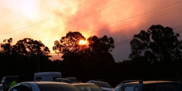 Residents wait at a gas station while bushfires erupt in Sydney's western suburb of Castlereagh. Photo / AFP