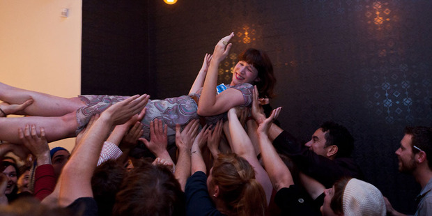 Many hands make light work: PledgeMe co-founder Anna Guenther crowdsurfs at a party in April to celebrate passing the $1 million fundraising mark.