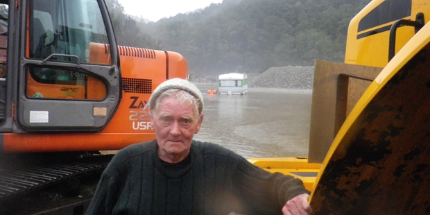 Alfie Smith waits for his caravan to be pulled from the storm-fed floodwaters at the Craig's Flat gravel pit near Reefton this morning. Photo / Greymouth Star
